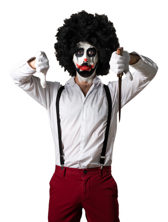 disapprove: Killer clown with knife making bad signal