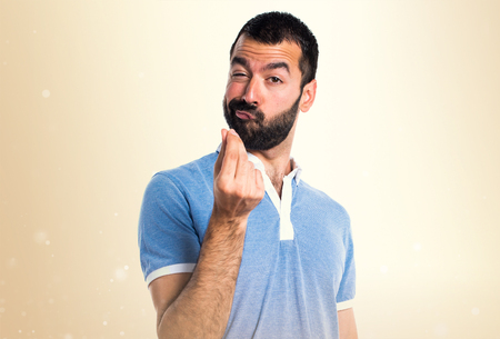 Man with blue shirt doing money gesture on ocher background Stock Photo