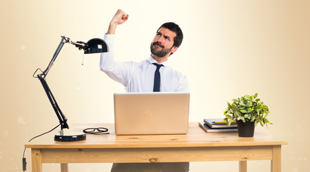 Lucky businessman in his office on ocher background Stock Photo