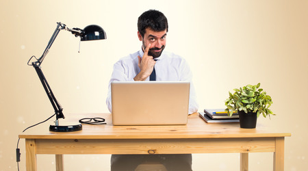 Businessman in his office showing something on ocher background Stock Photo