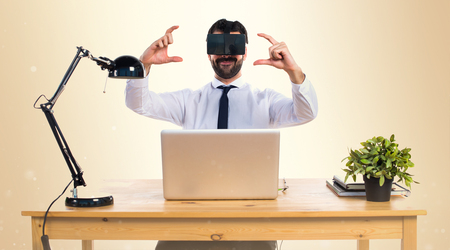 computer simulation: Businessman in his office using VR glasses holding something on ocher background Stock Photo