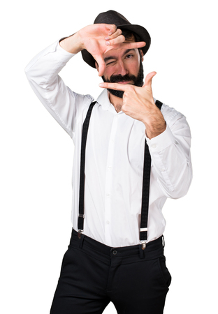 Hipster man with beard focusing with his fingers