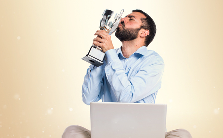 Man with laptop holding a trophy on ocher background