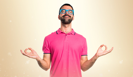 plead: Man with colorful clothes in zen position on ocher background Stock Photo