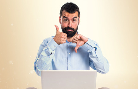 Man with laptop making good-bad sign on ocher background Stock Photo