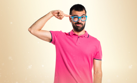 Man with colorful clothes making crazy gesture on ocher background Stock Photo