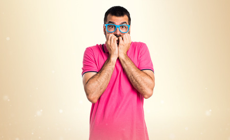 Frightened man with colorful clothes on ocher background