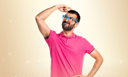 Man with colorful clothes thinking on ocher background