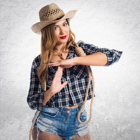 Sexy blonde woman cowgirl making time out gesture