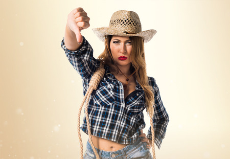Sexy blonde woman cowgirl making bad signal