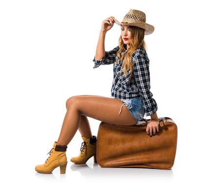 Sexy blonde woman cowgirl with vintage suitcase Stock Photo