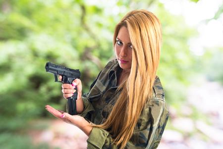 Military woman carrying a gun