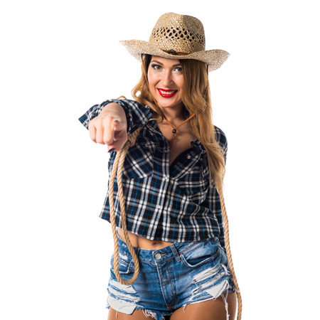 Sexy blonde woman cowgirl pointing to the front
