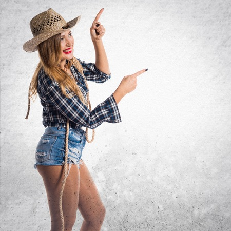 Sexy blonde woman cowgirl pointing to the lateral
