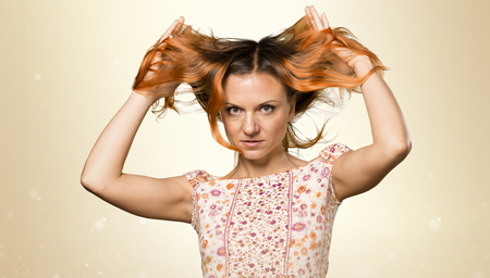 Pretty woman with orange hair on ocher background Stock Photo
