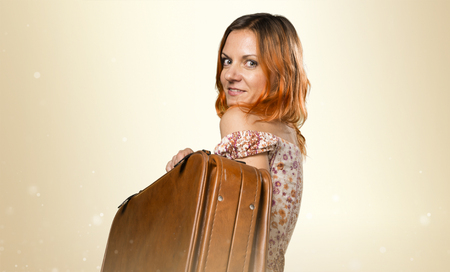 Pretty woman with orange hair holding a vintage briefcase on ocher background