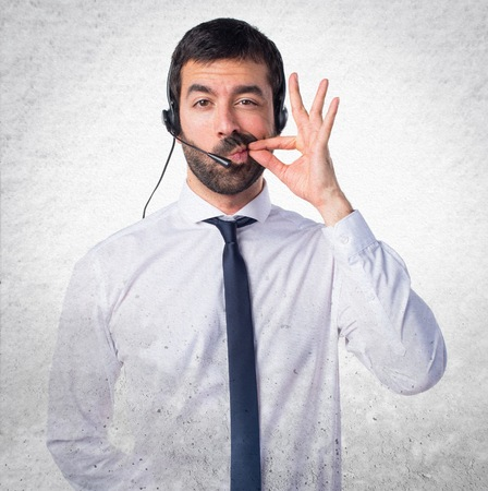 Young man with a headset making silence gesture on textured background