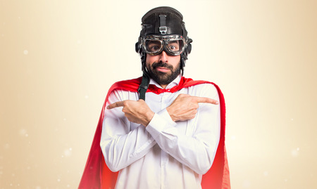 Crazy superhero man pointing to the laterals having doubts on ocher background Stock Photo