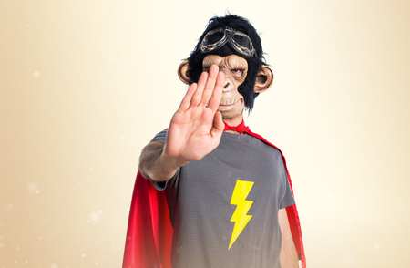 Superhero monkey man making stop sign on ocher background