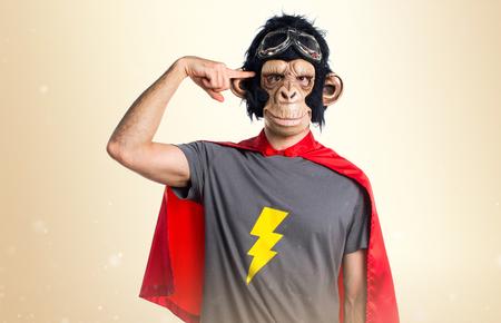 Superhero monkey man making crazy gesture on ocher background Stock Photo