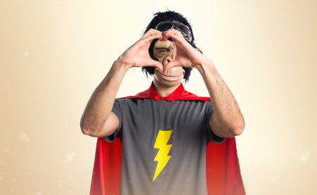 primates: Superhero monkey man making a heart with his hands on ocher background
