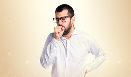 Handsome man with glasses coughing a lot on ocher background