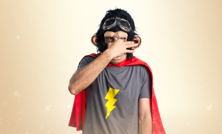 Superhero monkey man making smelling bad gesture on ocher background