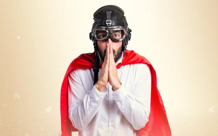 Crazy superhero man pleading on ocher background Stock Photo