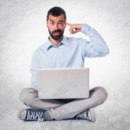 Man with laptop making crazy gesture on textured background Stock Photo