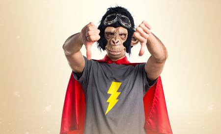 Superhero monkey man doing bad signal on ocher background Stock Photo