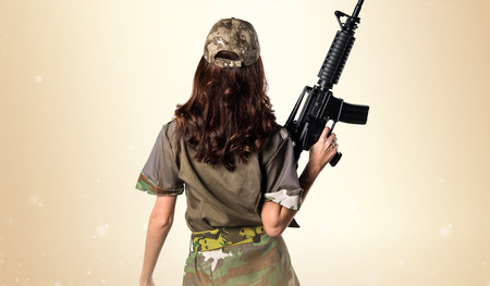 Military woman holding a rifle on ocher background