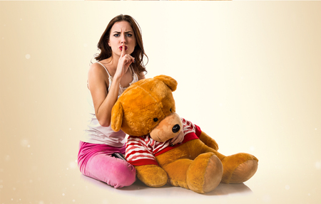 Girl with pajamas making silence gesture and playing with stuffed animal on ocher background