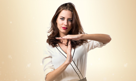 Beautiful brunette girl making time out gesture on ocher background
