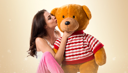 Girl with pajamas playing with a stuffed animal on ocher background