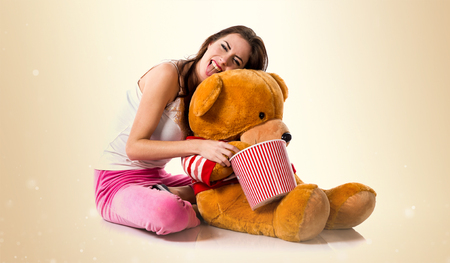 Happy girl with pajamas and holding a bowl of popcorns while playing with a stuffed animal on ocher background Stock Photo