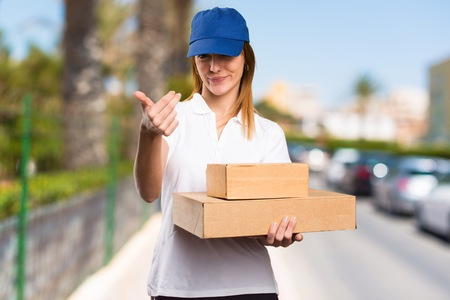 Delivery woman doing coming gesture on unfocused background