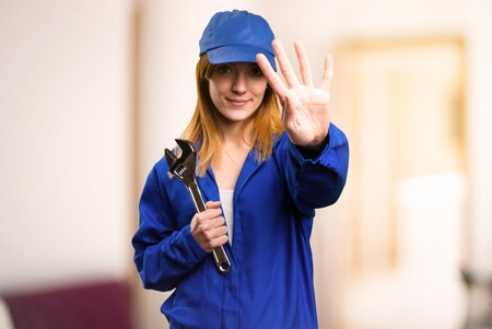 Delivery woman counting four on defocused background Stock Photo
