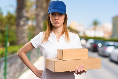 disapprove: Sad delivery woman on unfocused background
