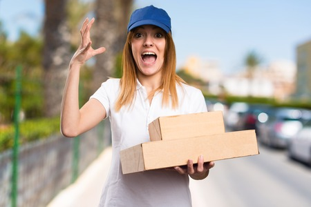 Frustrated delivery woman on unfocused background Stock Photo