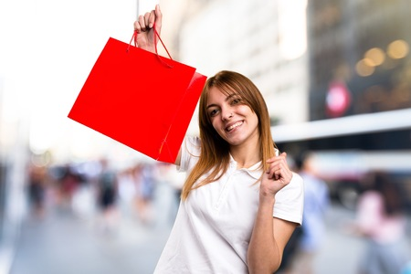 Happy Beautiful young girl with shopping bag on unfocused background