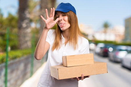Delivery woman making a joke on unfocused background Stock Photo