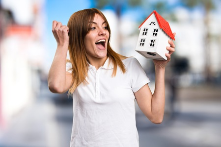 icone: Surprised Beautiful young girl holding a little house on unfocused background