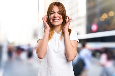 ignore: Beautiful young girl covering her ears on unfocused background Stock Photo