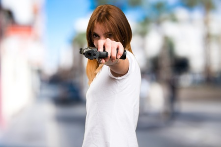 Beautiful young girl holding a pistol on unfocused background Stock Photo