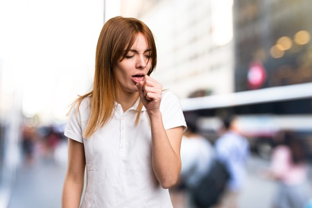 Beautiful young girl coughing a lot on unfocused background