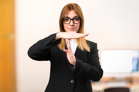 Young business woman making time out gesture on unfocused background