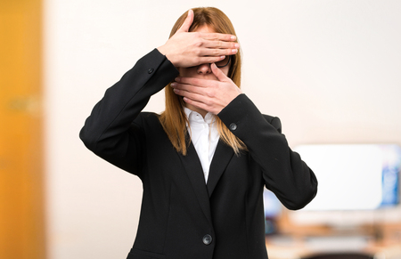 Young business woman covering her face on unfocused background