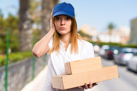 ignore: Delivery woman covering her ears on unfocused background Stock Photo