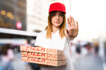 disgusted: Pizza delivery woman making stop sign on unfocused background