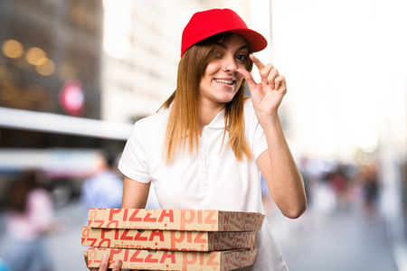 Pizza delivery woman making tiny sign on unfocused background Stock Photo